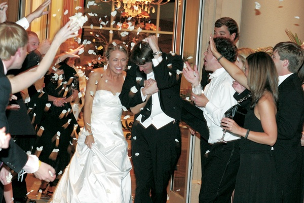 Guests toss flowers on bride and groom