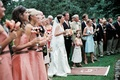 Wedding party and guests participate in Champagne toast in garden