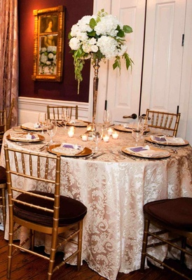 Gold plates and chairs with white flower centerpiece and taupe tablecloth
