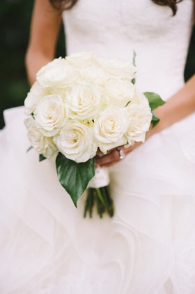Bride holding white roses and large leaves
