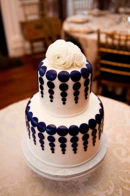 White fondant cake with purple dot design and ranunculus