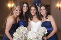 Bride with bridesmaids in Badgley Mischka dark blue dresses with light colored bouquets