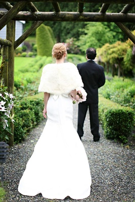 back view of fit and flare gown and white fur wrap
