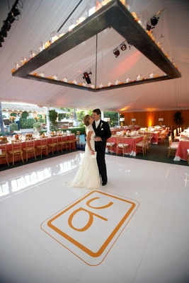 Orange wedding monogram on white dance floor