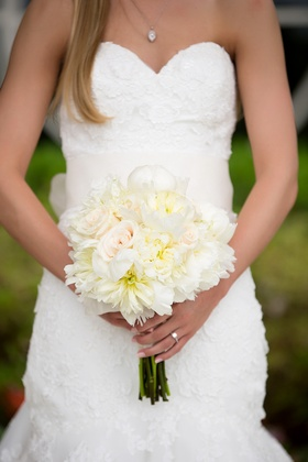 Bridal bouquet of white roses, white peonies, and dahlias with a bit of yellow and pink color