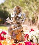 Outdoor Indian wedding ceremony with a golden Ganesh statue