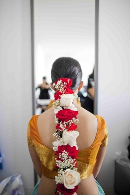 Bride's braided hair with red and white flowers