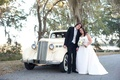 Bride and groom standing in front of classic pale yellow car