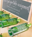 Wedding reception table assignment written on green wine bottles held by a wood board