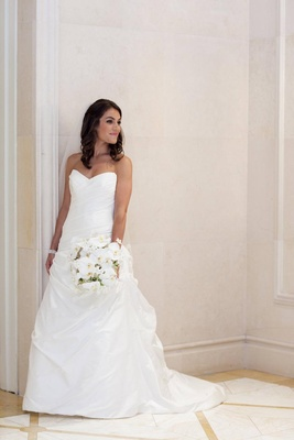 Bride in a strapless A-line Romona Keveza gown and white bouquet