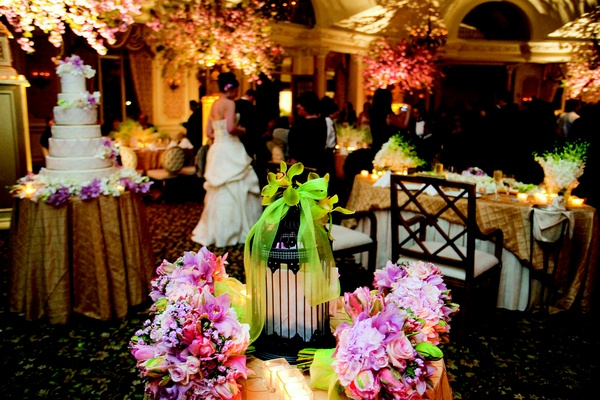 Bridesmaids' bouquets of pink and light purple flowers decorate a table with a lantern