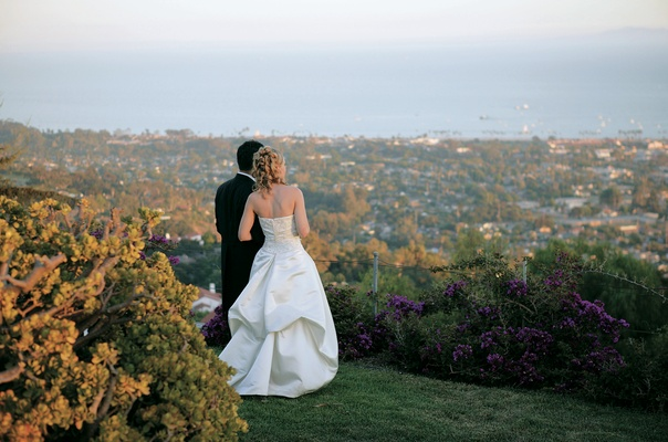 Groom and bride in ball gown look out at ocean