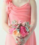Bridesmaid bouquet of pink peonies, roses, and orange garden roses and dusty miller