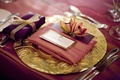 Purple favor box on golden charger plate