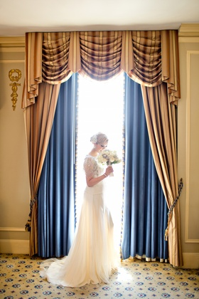 Bride in a Jenny Packham dress holds white flower bouquet in front of a window