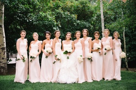 Bride with bridesmaids wearing one-shoulder dresses