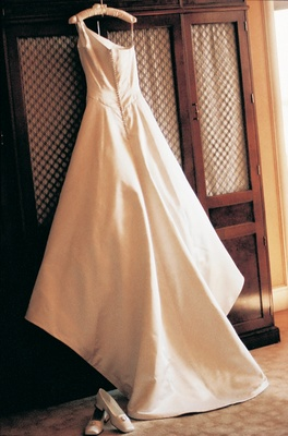 Back of one-shouldered wedding gown hangs in boudoir