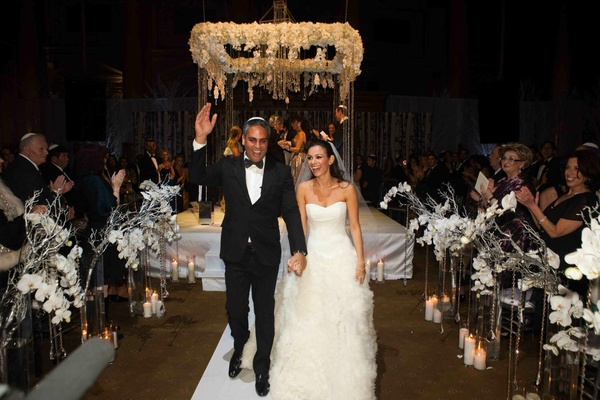 Bride and groom walk up white aisle with winter flower arrangements
