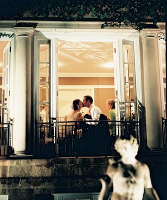 Bride and groom kiss at reception through window view