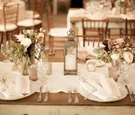 Wood table topped with lace runner and lantern