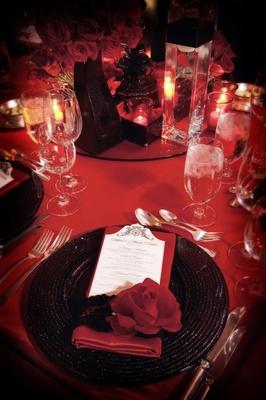 Bold décor with ebony plates and crimson napkins