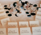 Simple escort cards on a table with white flowers