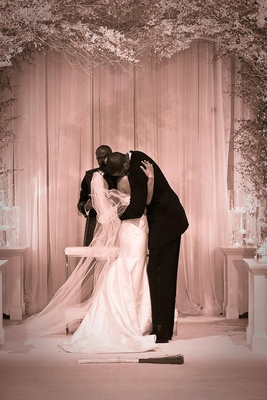 Sepia photo of couple kissing before jumping the broom