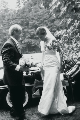 Black and white photo of bride getting out of classic Mercedes wedding car