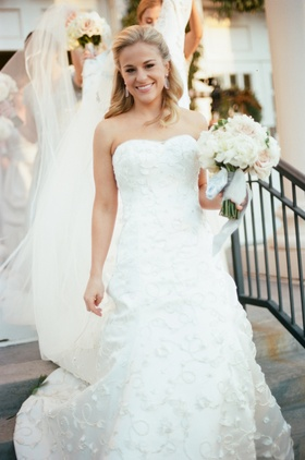 Bride wearing strapless wedding dress with flower embroidery