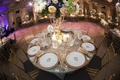 Wedding reception table with gold-rimmed plates, golden napkins, candles, and flowers