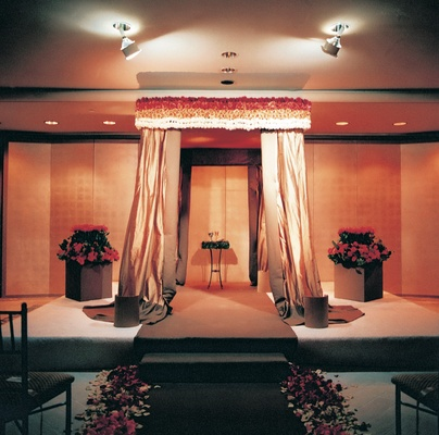 Red, orange, and cream indoor ceremony decorations