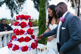 newlyweds cut white cake with red and purple flowers