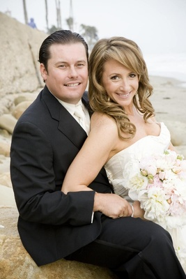 Bride and groom smile on rocky beach