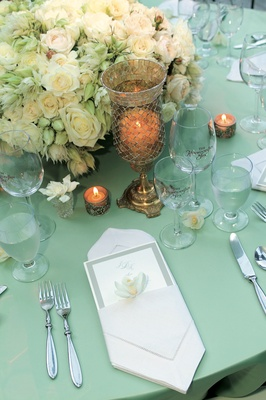Reception dinner table with a light green table cloth, white and light green flowers and candles