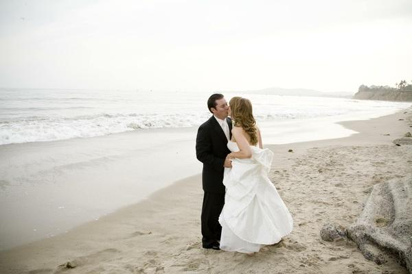 Bride and groom kiss on beach in Santa Barbara