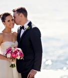Groom kisses bride's cheek in front of Ocean at Terranea Resort