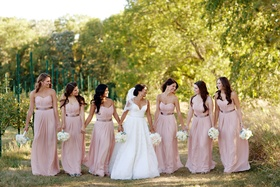 Bride in lace gown and veil with bridesmaids in long pink dresses with brown sashes white bouquet