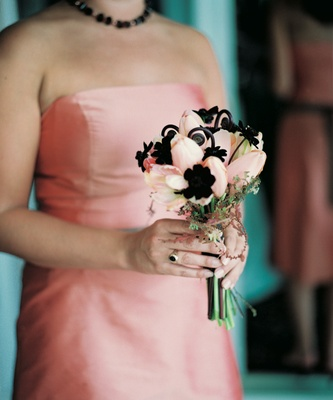 Bridesmaid holds pink tulip bouquet with black flowers