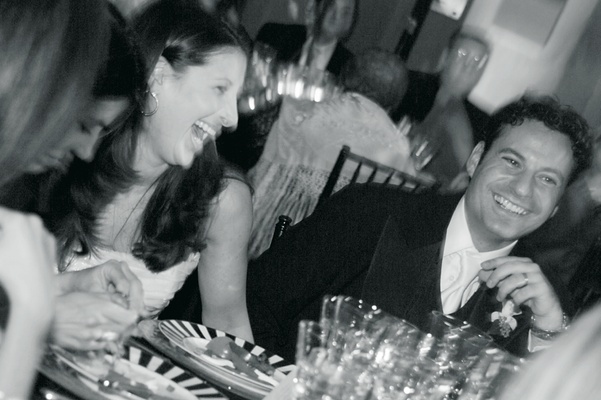 Black and white photo of bride and groom sitting at a reception table
