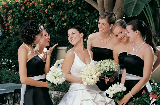 black dresses with white ribbon belt and bride carrying bouquet