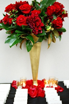 Gold trumpet vase filled with red flowers