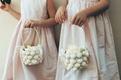 flower girls carry baskets covered in seashells