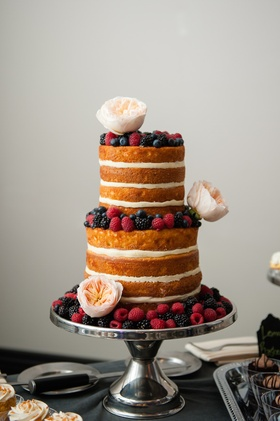 Cake without frosting topped with raspberries and flowers