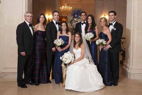 Bride in a strapless Romona Keveza gown, veil, and white bouquet with loved ones