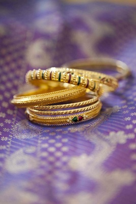 Golden bangles with red and green enamel touches