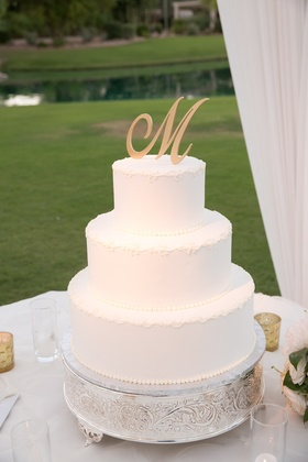 White wedding cake with gold initial topper