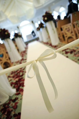 Beginning of aisle tied with white ribbon in bow