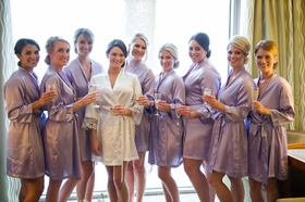 Bridesmaids in purple robes in bridal suite