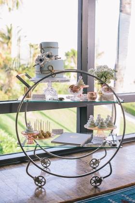 Wedding reception with an art deco dessert cart carrying a blue wedding cake, macarons, mini cakes