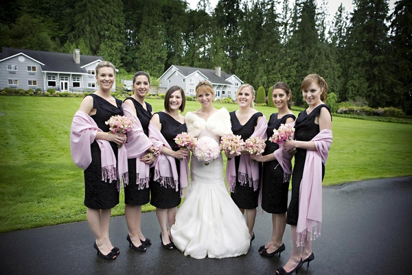 bridesmaids wear black dresses and lavender pashminas
